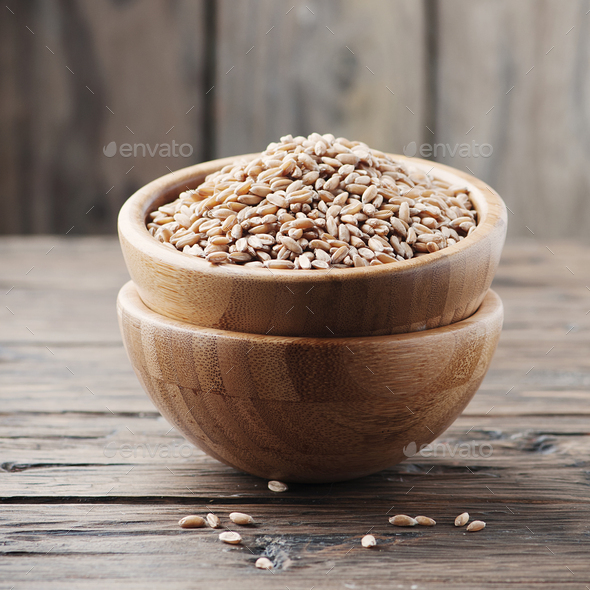 Raw pearl barley on the wooden table - Stock Photo - Images