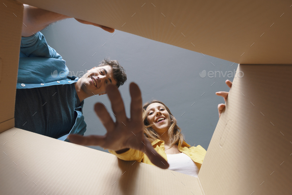 Happy couple opening a cardboard box and looking inside - Stock Photo - Images