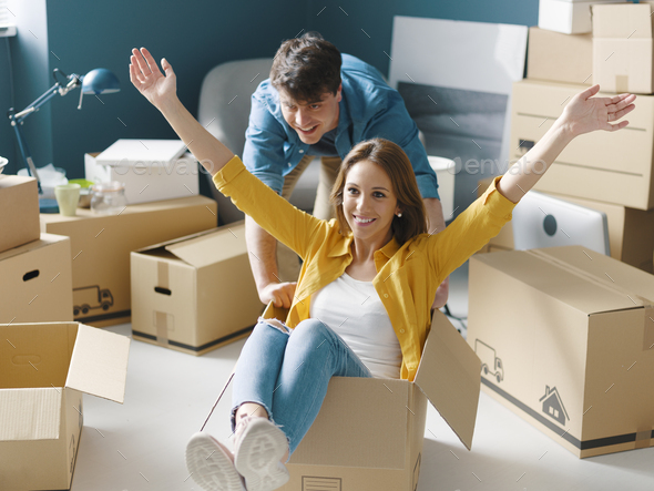 Cheerful young couple moving in their new house - Stock Photo - Images