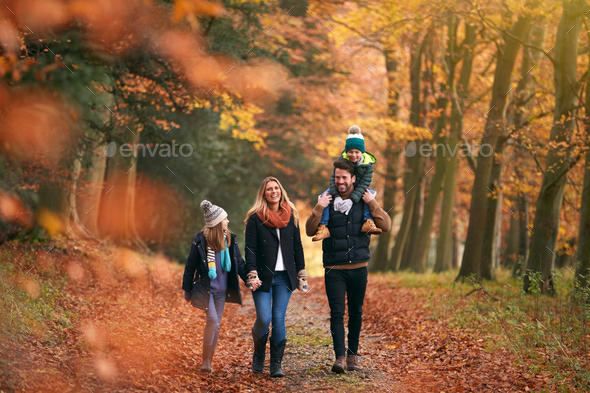 Family Walking Along Autumn Woodland Path With Father Carrying Son On Shoulders - Stock Photo - Images