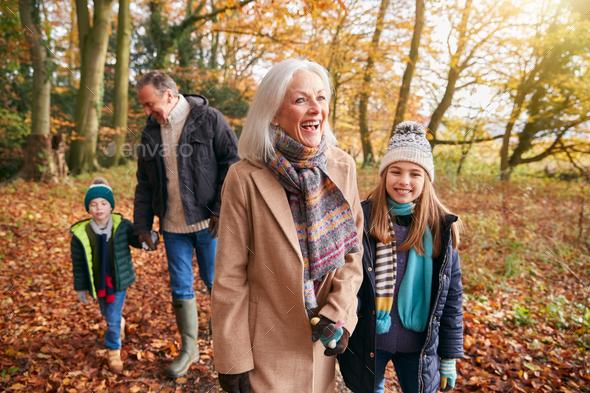 Grandparents With Grandchildren Enjoying Walk Along Autumn Woodland Path Together - Stock Photo - Images