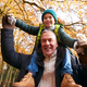 Portrait Of Grandfather Giving Grandson Ride On Shoulders As They Walk Along Autumn Woodland Path - PhotoDune Item for Sale