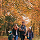 Family Walking Arm In Arm Along Autumn Woodland Path Together - PhotoDune Item for Sale