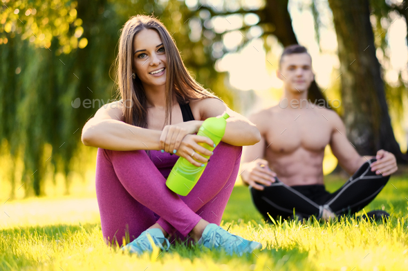 Sporty couple relaxing after fitness and yoga exercises. - Stock Photo - Images