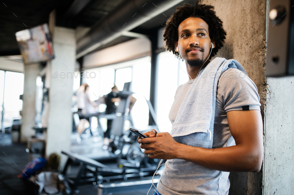 Young muscular man using mobile phone at the gym in exercise break - Stock Photo - Images