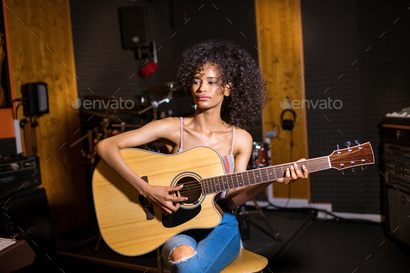 Trendy young black woman playing guitar - Stock Photo - Images