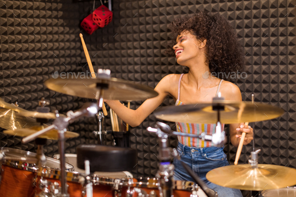 Young black female drummer in a recording studio - Stock Photo - Images