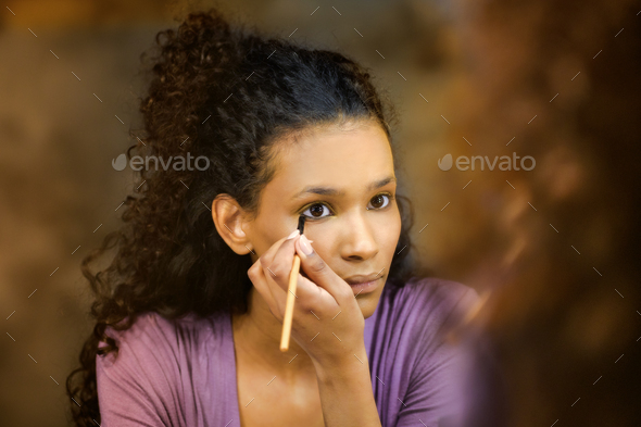 Attractive young black woman applying makeup - Stock Photo - Images