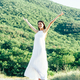 Full length of young brunette hair woman posing in summerfield in white dress. Mountain view. - PhotoDune Item for Sale