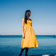 Portrait of young brunette girl with wet hair in yellow dress in the beach. Summer sea background - PhotoDune Item for Sale