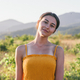 Portrait of young brunette woman posing in summer field in yellow dress. Mountain background view. - PhotoDune Item for Sale