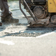 Worker using compactor to finish patching bump in the road - PhotoDune Item for Sale