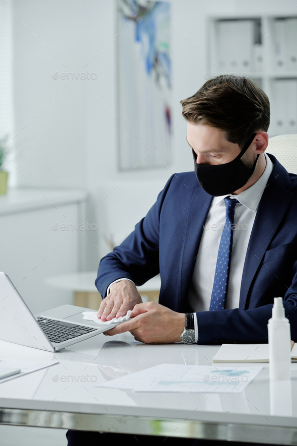 Disinfecting laptop with wet napkin - Stock Photo - Images