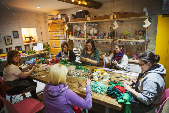 Group of people, women around a table in workshop, making paper flower wreaths.
