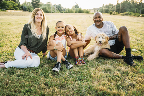 Portrait of mixed-race family in field with labradoodle puppy - Stock Photo - Images
