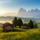 Chalets at Seiser Alm with Langkofel mountain in background at sunrise, Dolomites, Italy - PhotoDune Item for Sale