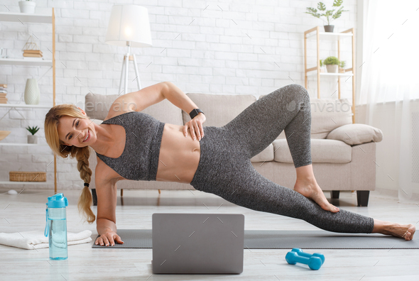 Fitness lessons online at home. Woman in sportswear makes side plank on mat on floor with laptop - Stock Photo - Images