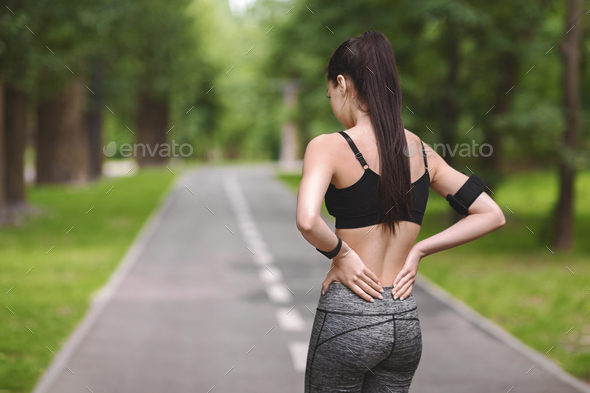 Back Pain. Young fit woman rubbing muscles of her lower back outdoors - Stock Photo - Images