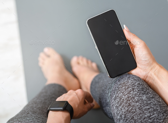 Devices for sport. Woman with smart watch and phone in her hand with blank screen, sits on mat - Stock Photo - Images