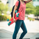 Asian woman with skateboard in modern city - PhotoDune Item for Sale