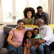 Mixed race family spending time together sitting on a couch - PhotoDune Item for Sale
