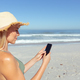 Woman using smartphone on the beach - PhotoDune Item for Sale