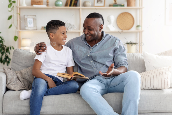 Mature Black Father And His Preteen Son Reading Book At Home Together