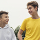 Two happy young teenage boys standing chatting - PhotoDune Item for Sale