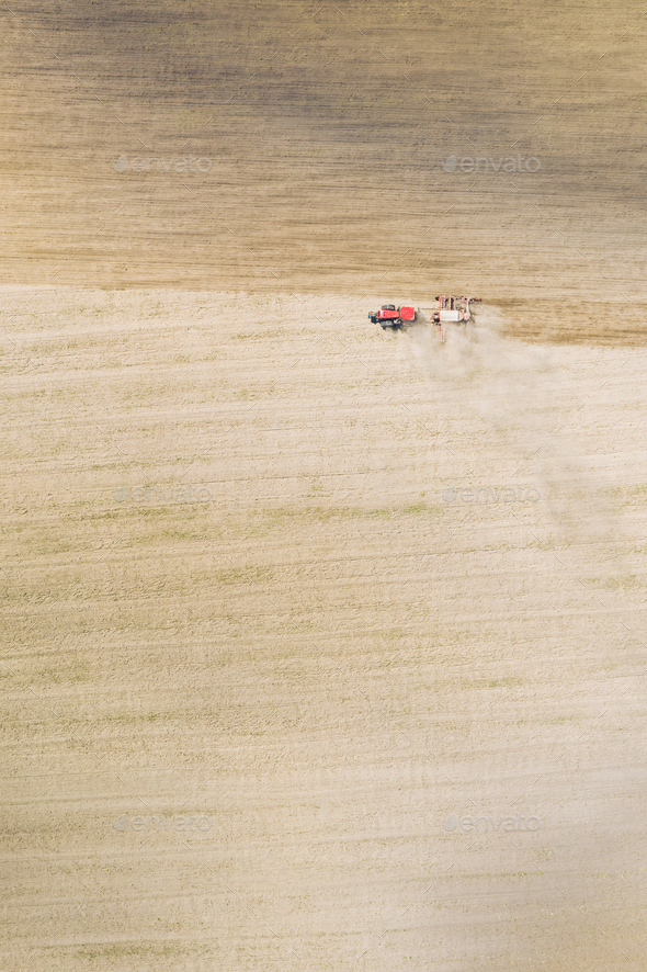 Aerial View. Tractor With Seed Drill Machine Sowing The Seeds For Crops In Spring Season. Beginning - Stock Photo - Images