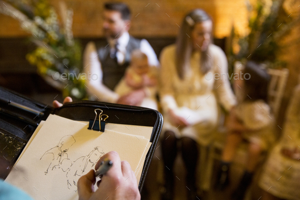 Over the shoulder view of artist sketching family during naming ceremony in an historic barn. - Stock Photo - Images