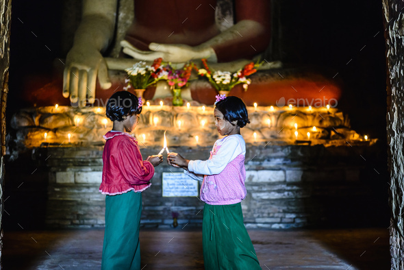 55054,Asian girls lighting candles in Buddhist temple - Stock Photo - Images