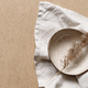 Minimalist ceramic bowl with dry plant over kraft paper background. - PhotoDune Item for Sale