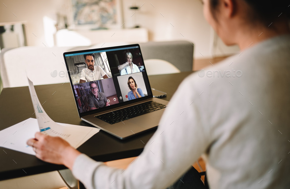Businesswoman at home having a video conference with her team - Stock Photo - Images