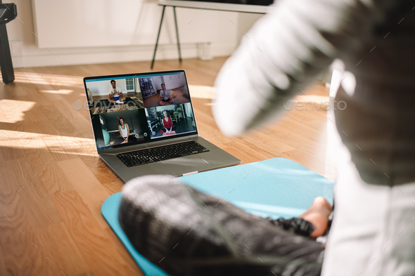 Woman conducting virtual fitness classes over video conference - Stock Photo - Images