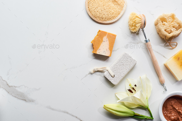 Natural Clay Mask, Soap Pieces, Body Brush, Pumice Stone And Loofah Near Fresh Flower on Surface - Stock Photo - Images