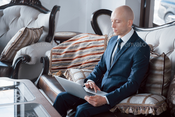 Confident handsome businessman sitting in luxury interior - Stock Photo - Images