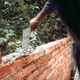Worker placing and installing bricks on exterior wall on house construction - PhotoDune Item for Sale