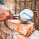 construction worker laying bricks and building walls on construction site - PhotoDune Item for Sale