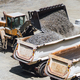 wheel loader working on construction site and loading gravel on dumper trucks. - PhotoDune Item for Sale