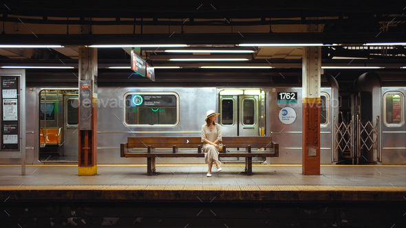 Young woman waiting for a train at the station in the subway - Stock Photo - Images