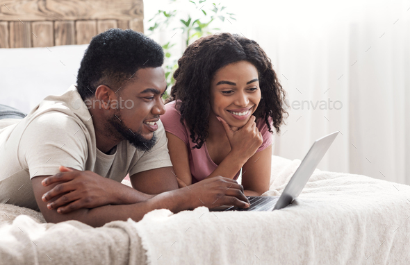 Positive african lovers using laptop together, bedroom interior