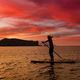 Stand up paddle boarding on a quiet sea with warm summer sunset colors - PhotoDune Item for Sale