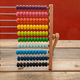 School abacus with colorful beads on wooden desk, close up view - PhotoDune Item for Sale