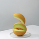 Flying cut piece of melon on white table - PhotoDune Item for Sale