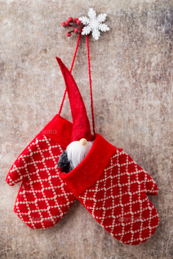 Red mittens gloves on christmas wooden background.