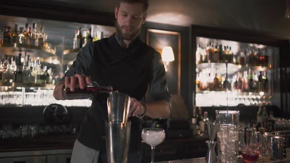 Bartender Pouring Alcohol in Beaker Then in Glass with Ice, Demonstrating His Skills