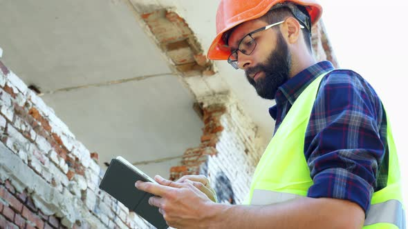 An Engineer Builder in a Helmet Is Calculating the Building Demolition Plan and Looking