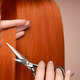 Hairdresser cuts long red hair with scissors - PhotoDune Item for Sale