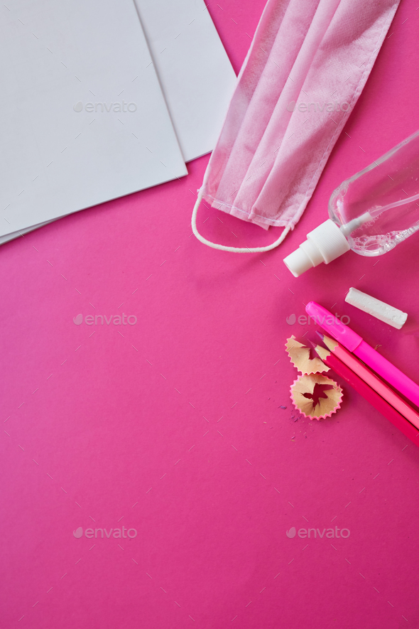 School supplies, protective mask and antiseptic on a pink background - Stock Photo - Images