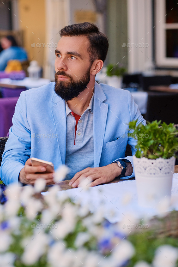 Stylish bearded male in a blue jacket using smartphone. - Stock Photo - Images
